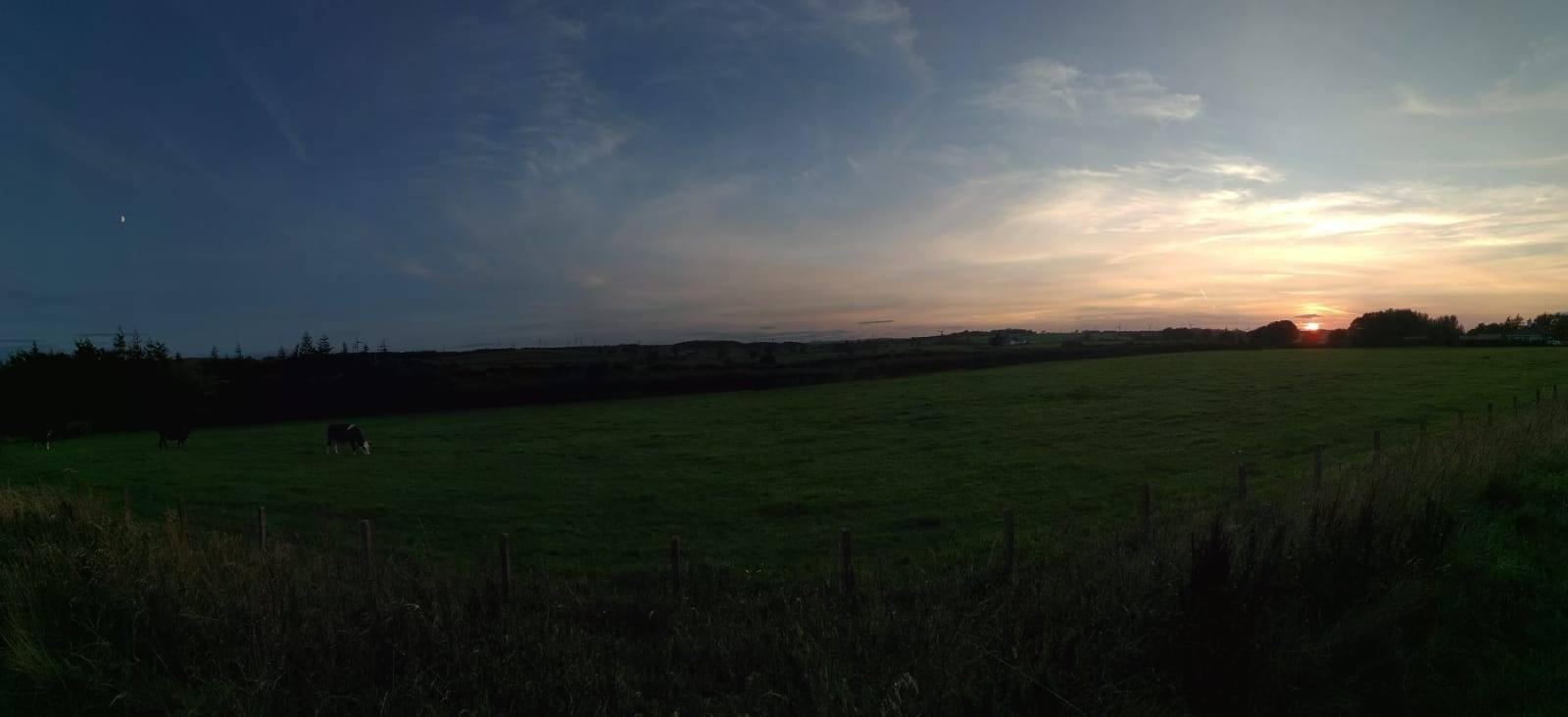 A photo of the Scottish countryside. The sky is split between the moon and the night on the left and the sunset on the right.